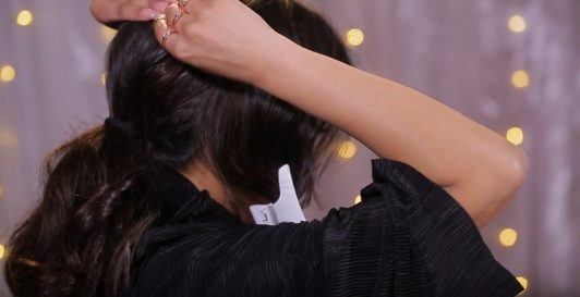 Nikki Secrets putting hair into ponytail