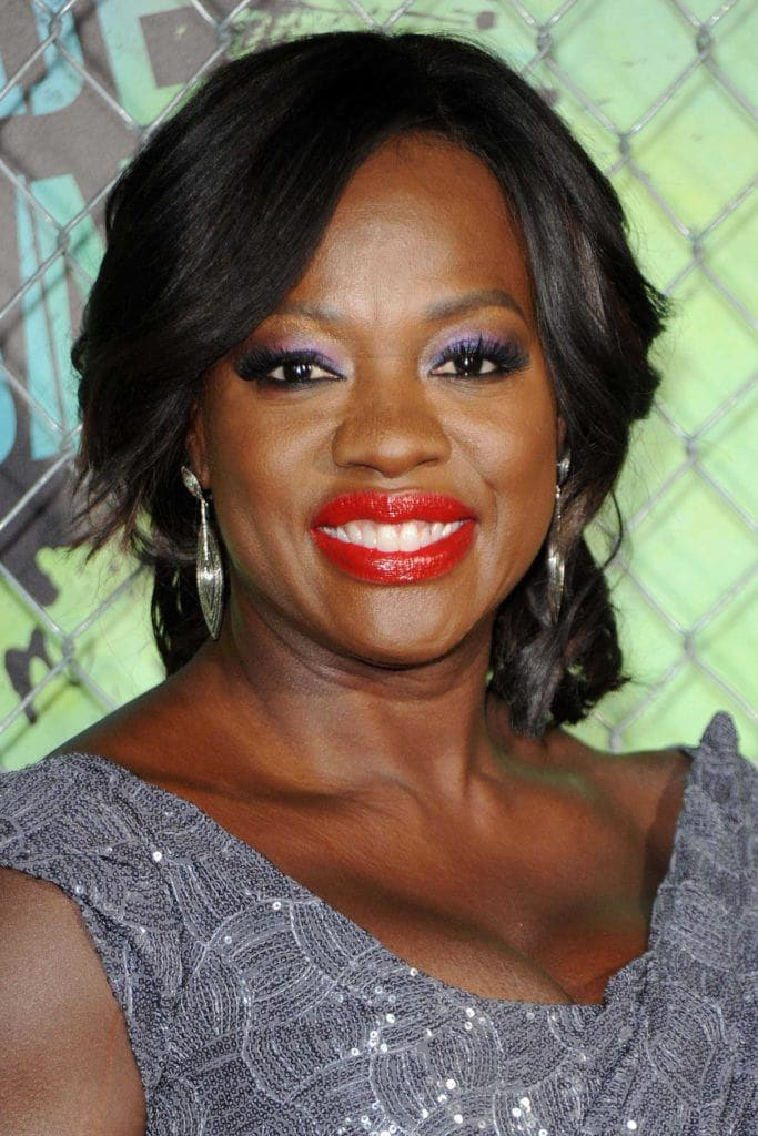 Viola Davis on the red carpet wearing a purple dress with her black natural hair worn in an updo