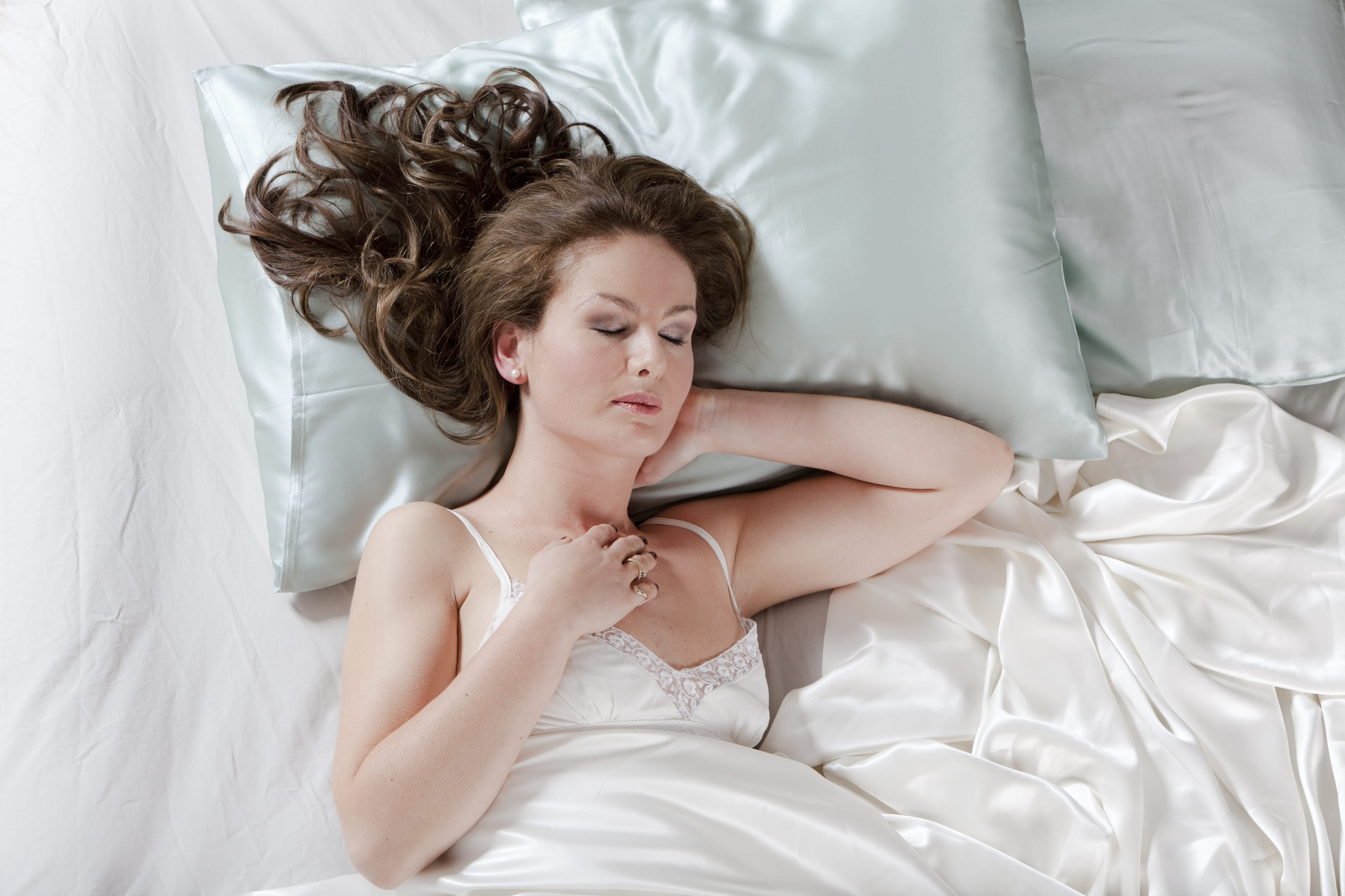 How to get rid of frizzy hair: Woman with long wavy brown hair laying in bed with silk sheets.