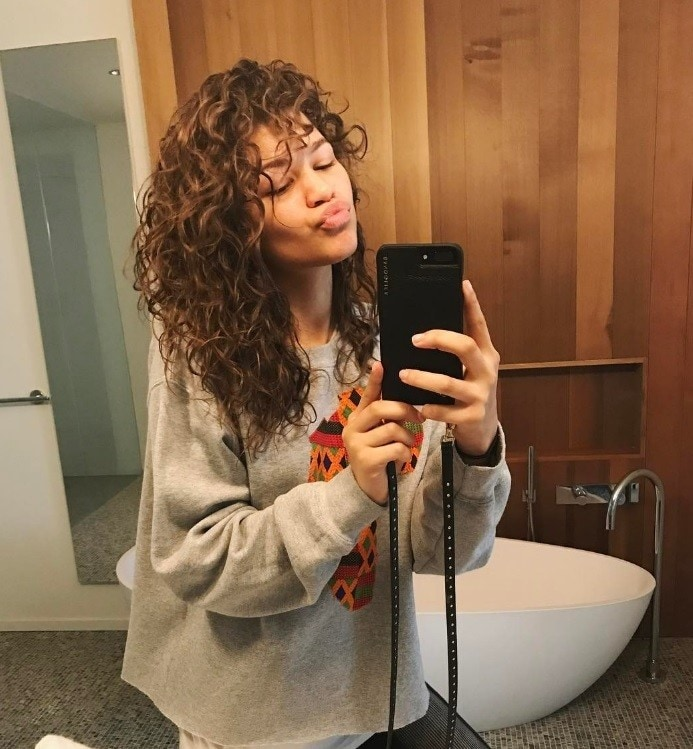 Zendaya with curly brown hair taking a selfie in the mirror wearing a great sweater with a print on it