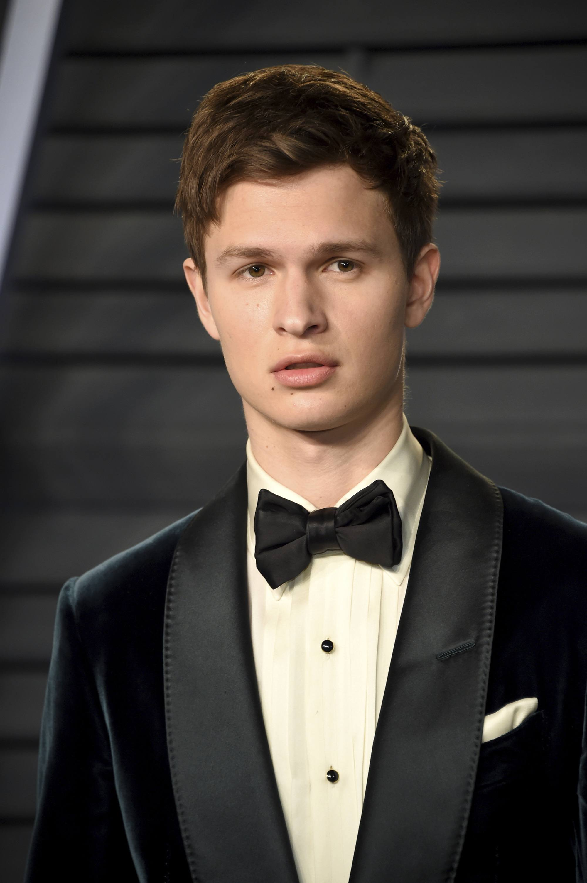 close up shot of ansel elgort wearinhg black suit with bow tie, with his hear styled into a textured mid length crop at the 90th Academy Awards