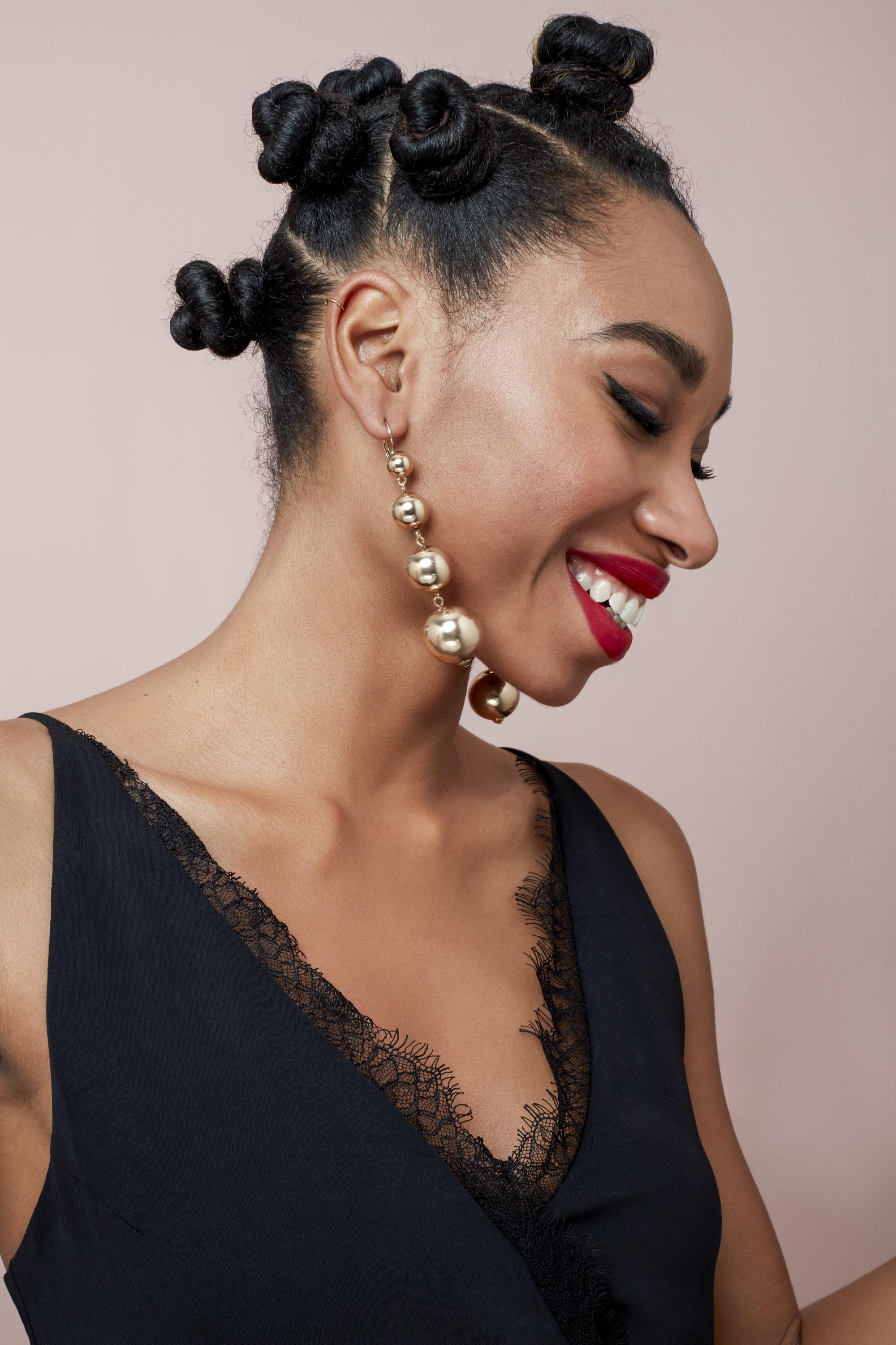 Natural hairstyles for Valentine's Day: Side shot of woman with bantu knots, wearing satin dress with gold earrings in the studio