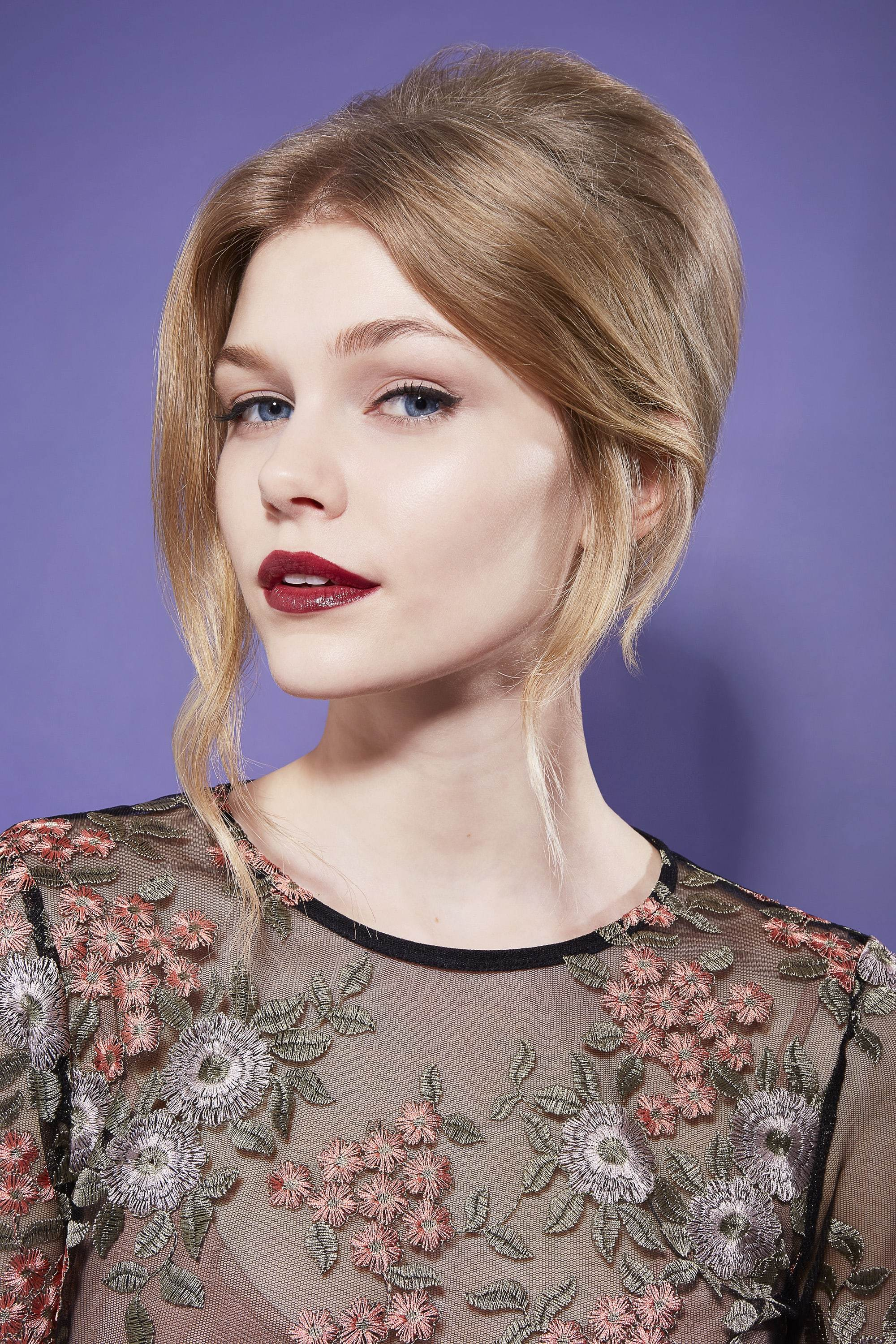 close up shot of model with romantic beehive updo hairstyle, wearing dark purple lipstick and floral top