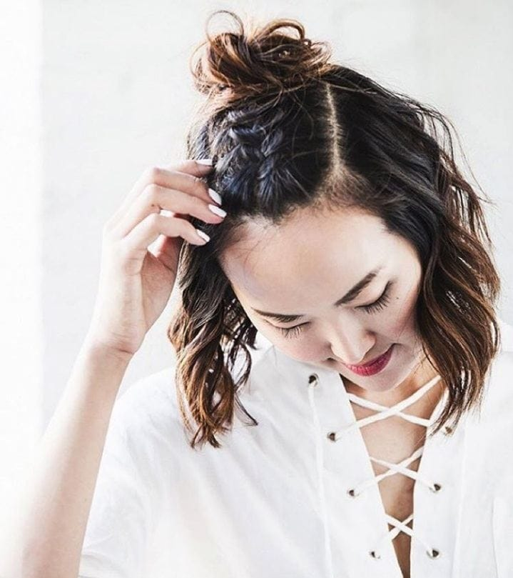 Gym hairstyles for thick hair: Brunette girl with wavy bob hair braided down the middle in a unicorn braid and tied in a mini bun