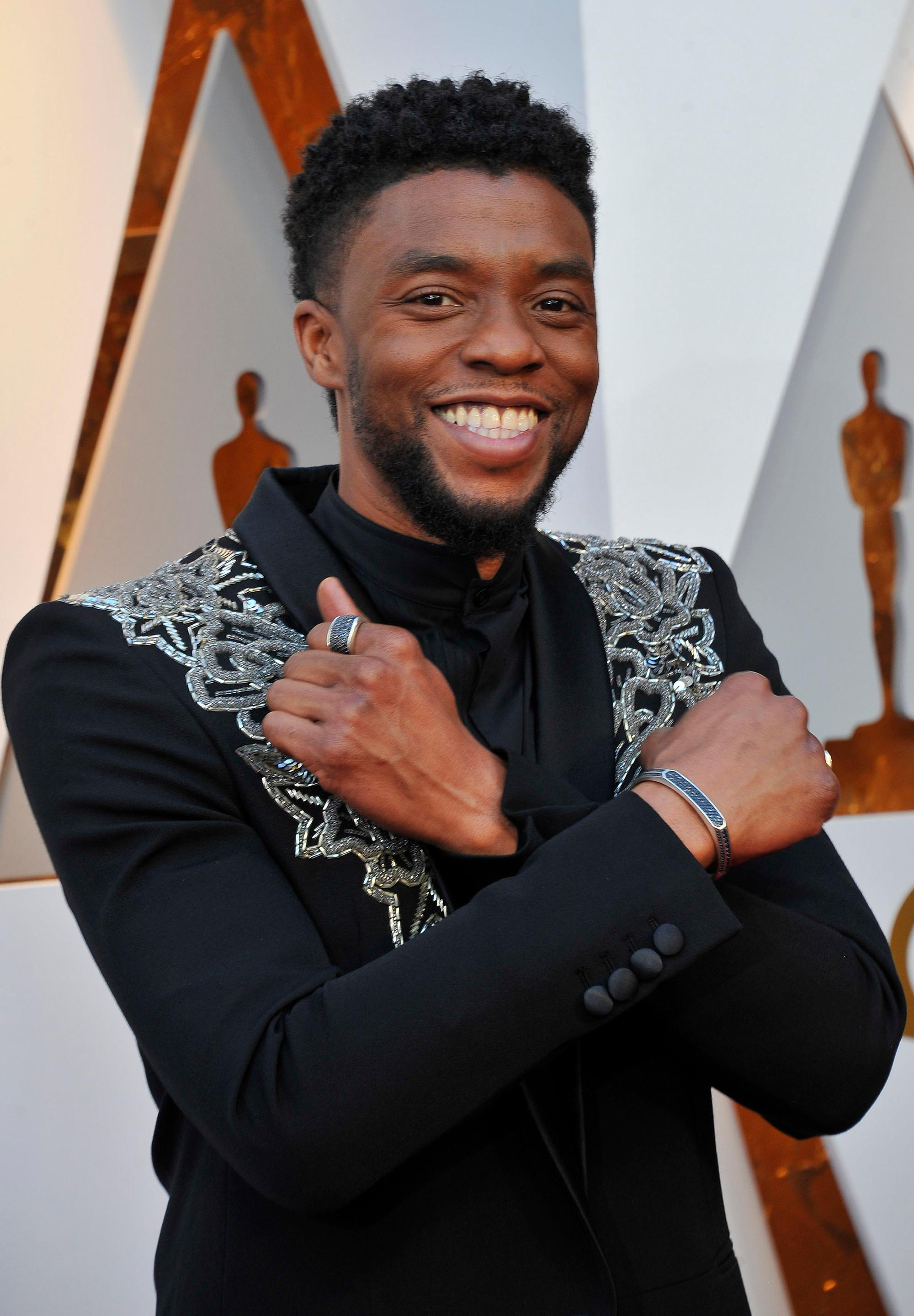 close up shot of chadwick boseman with black suit with silver designs on it wearing his black hair short in a south of france haircuit and posing at the 90th Academy Awards