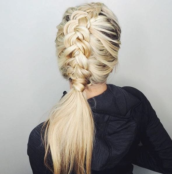 Gym hairstyles for thick hair: Back view of a woman with light blonde hair in chunky dutch braid into a ponytail