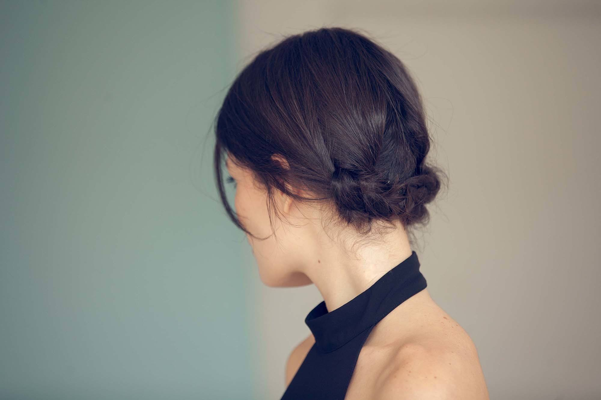 Club hairstyles: Shot from behind of a brunette with a braided updo, wearing a black halterneck top