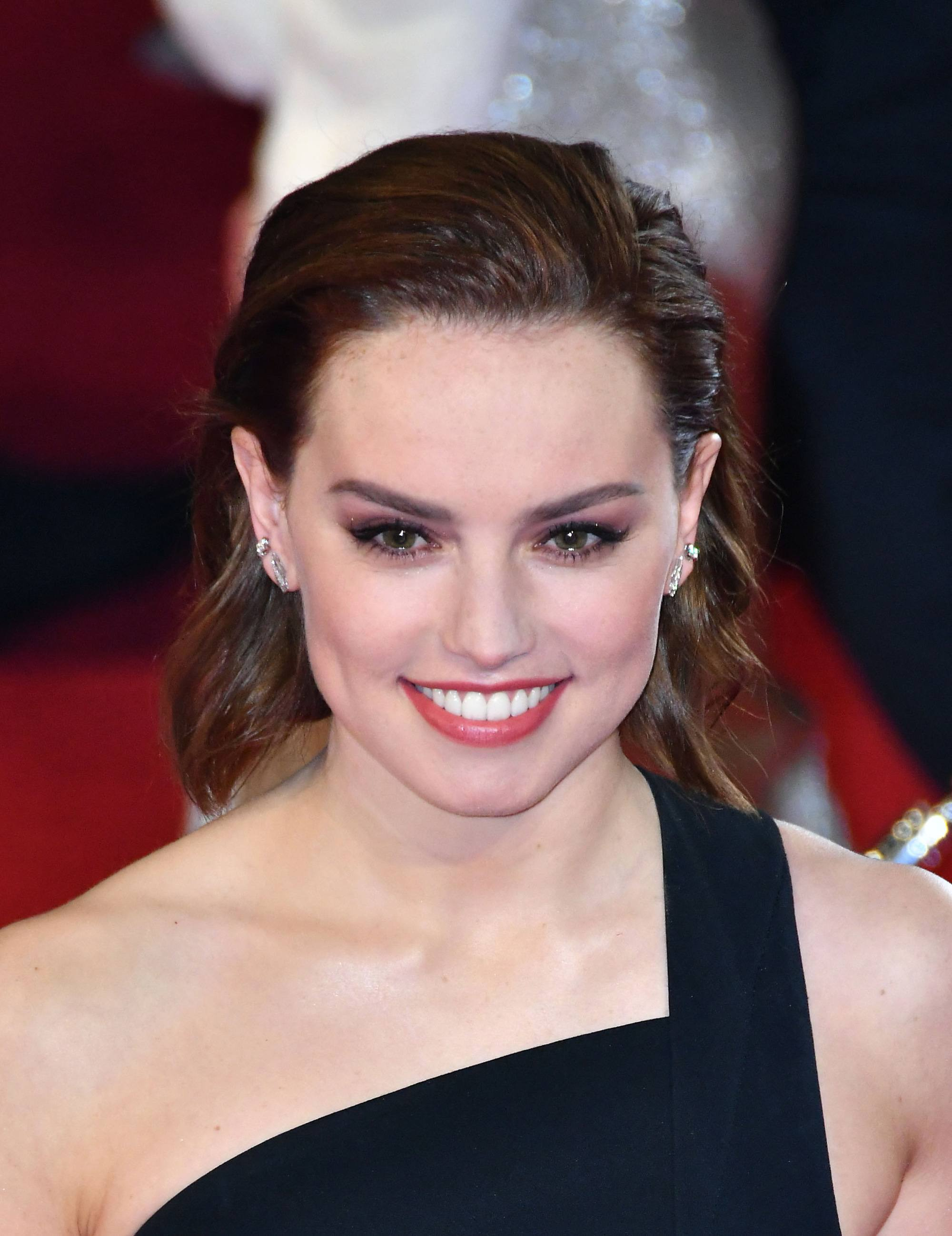 Daisy Ridley in black dress with her brunette hair slicked back