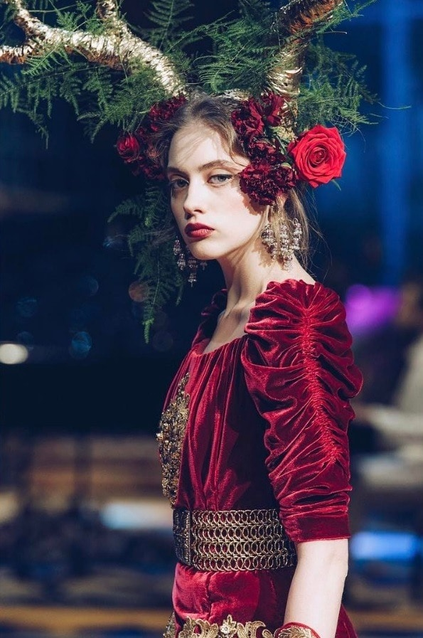 model with floral headpiece at the Dolce & Gabbana couture show wearing a red velvet dress and golden accessories
