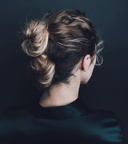 Gym hairstyles for thick hair: Back view of a woman with brown blonde ombre hair in two double stacked buns