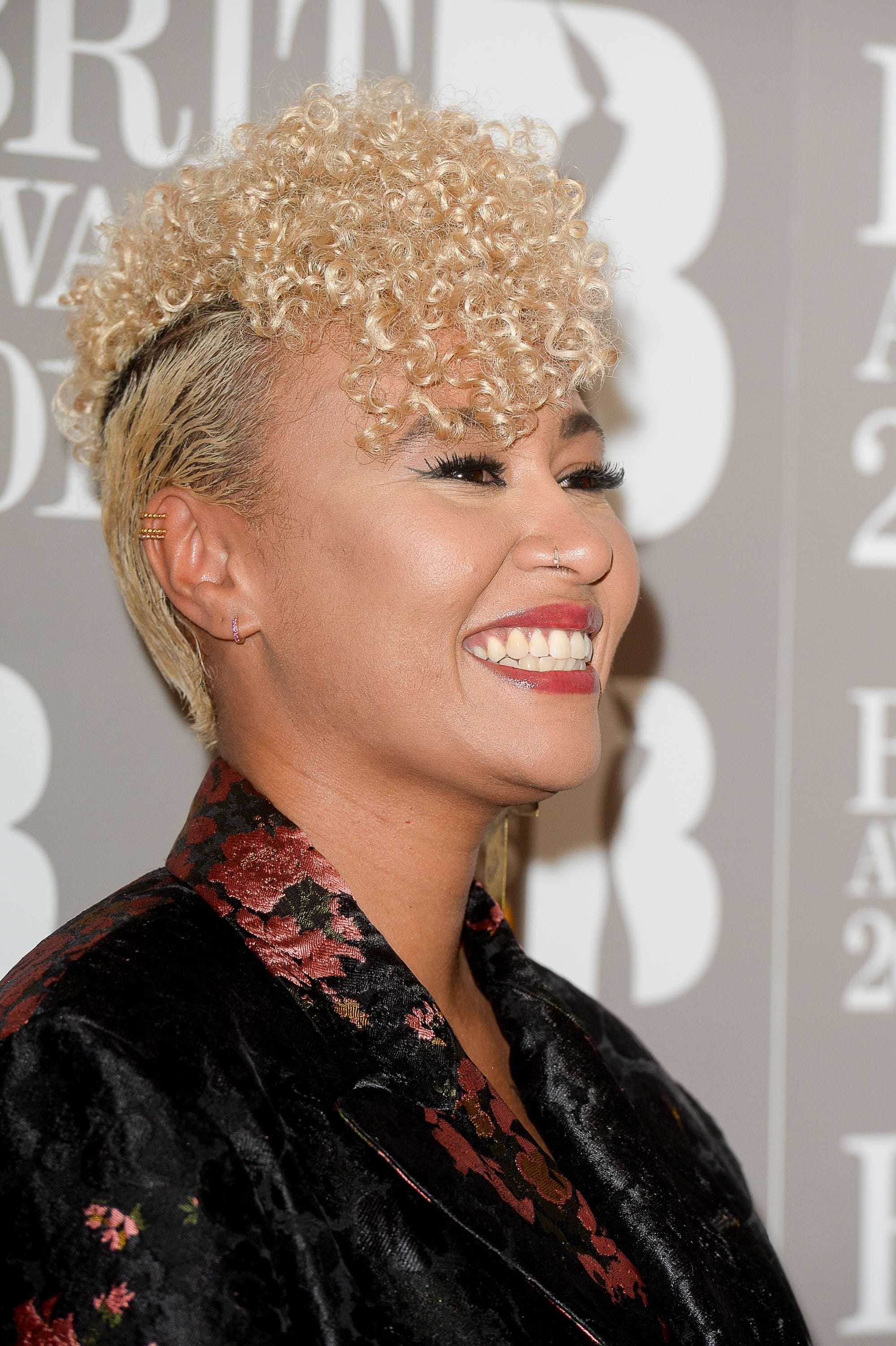 close up shot of Emeli Sande curly fauxhawk hairstyle, wearing black and floral suit and posing on the brit awards 2017 red carpet