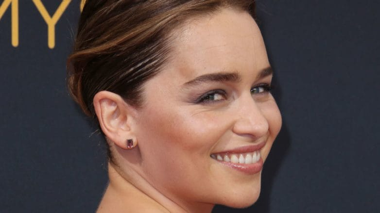Game of Thrones actress Emilia Clarke on the red carpet with her brunette hair in a sleek low bun