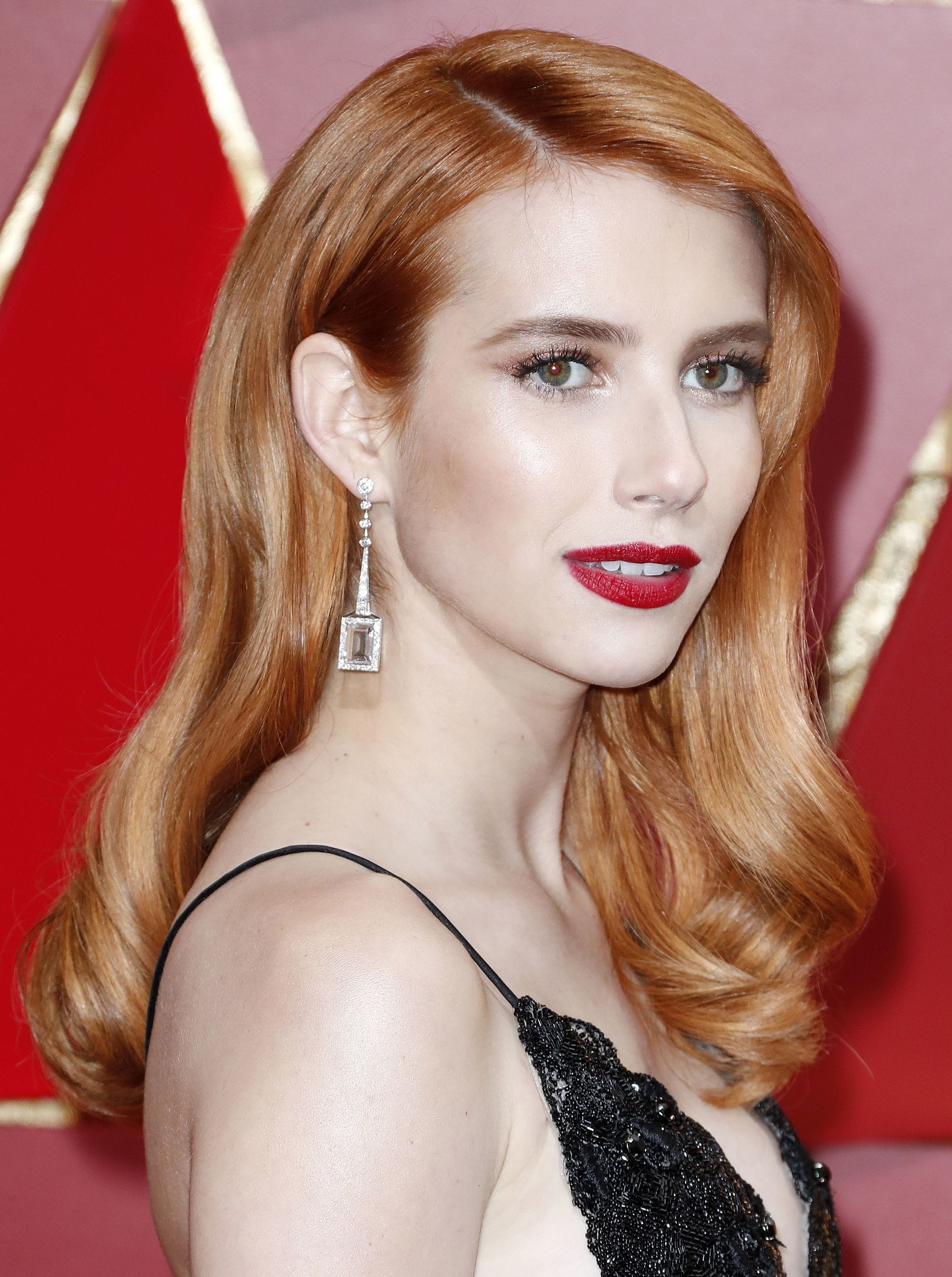 emma roberts at the oscars 2017 in a black lace dress with red lipstick and bright copper red hair