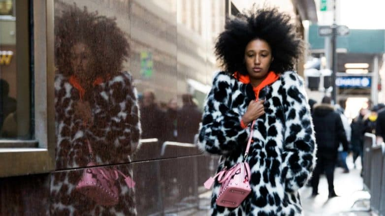 nyfw street styler wearing a spotty animal print fur coat, an orange hoodie, mom jeans and converse with voluminous natural afro hair