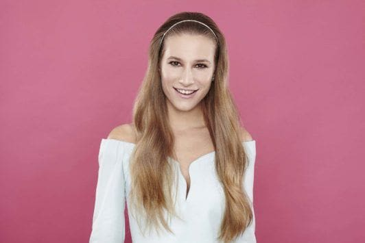 girl with long wavy light brown hair and white headband