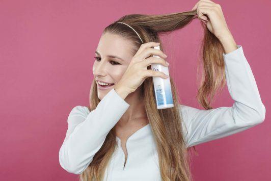 girl backcombing her long brown hair