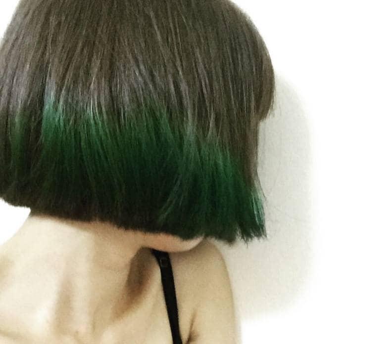 Short ombre hair: Woman with emerald green ombre hair cut into a sleek bob cut