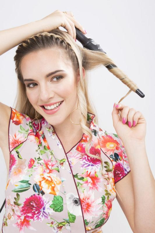 woman with long blonde curling her hair with a curling wand
