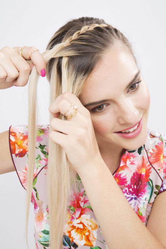woman with long blonde hair french braiding her hair