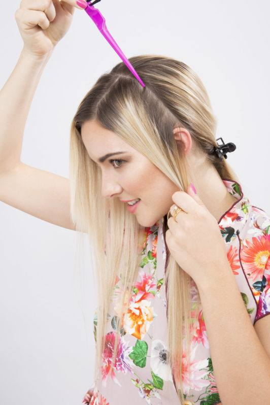 woman with long blonde hair sectioning her with a comb