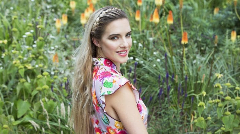 woman with long blonde hair and a headband braid wearing a floral dress outdoors