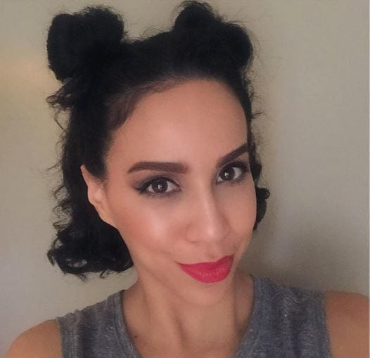 Dark haired woman with two half-up mini buns wearing red lipstick