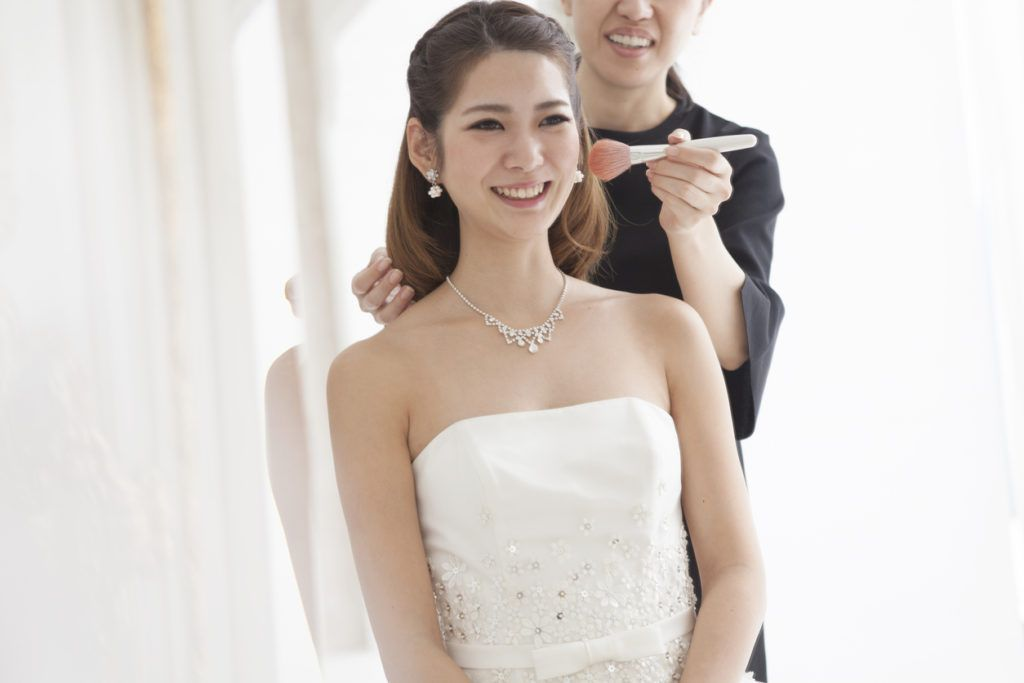 asian bride wearing strapless white gown with her long brunette hair styled into a half up half down look