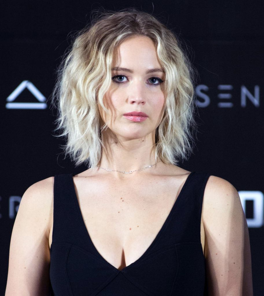 jennifer lawrence on the red carpet in a black v neck dress with a blonde shaggy lob hairstyle
