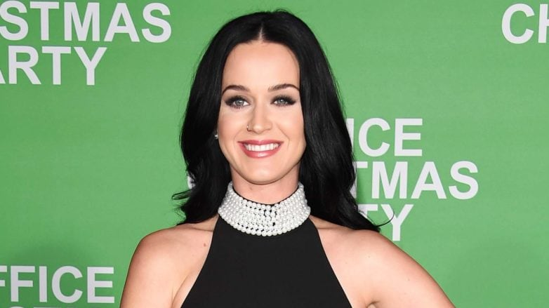 Katy Perrt wearing all black and a jewelled necklace with long dark hair