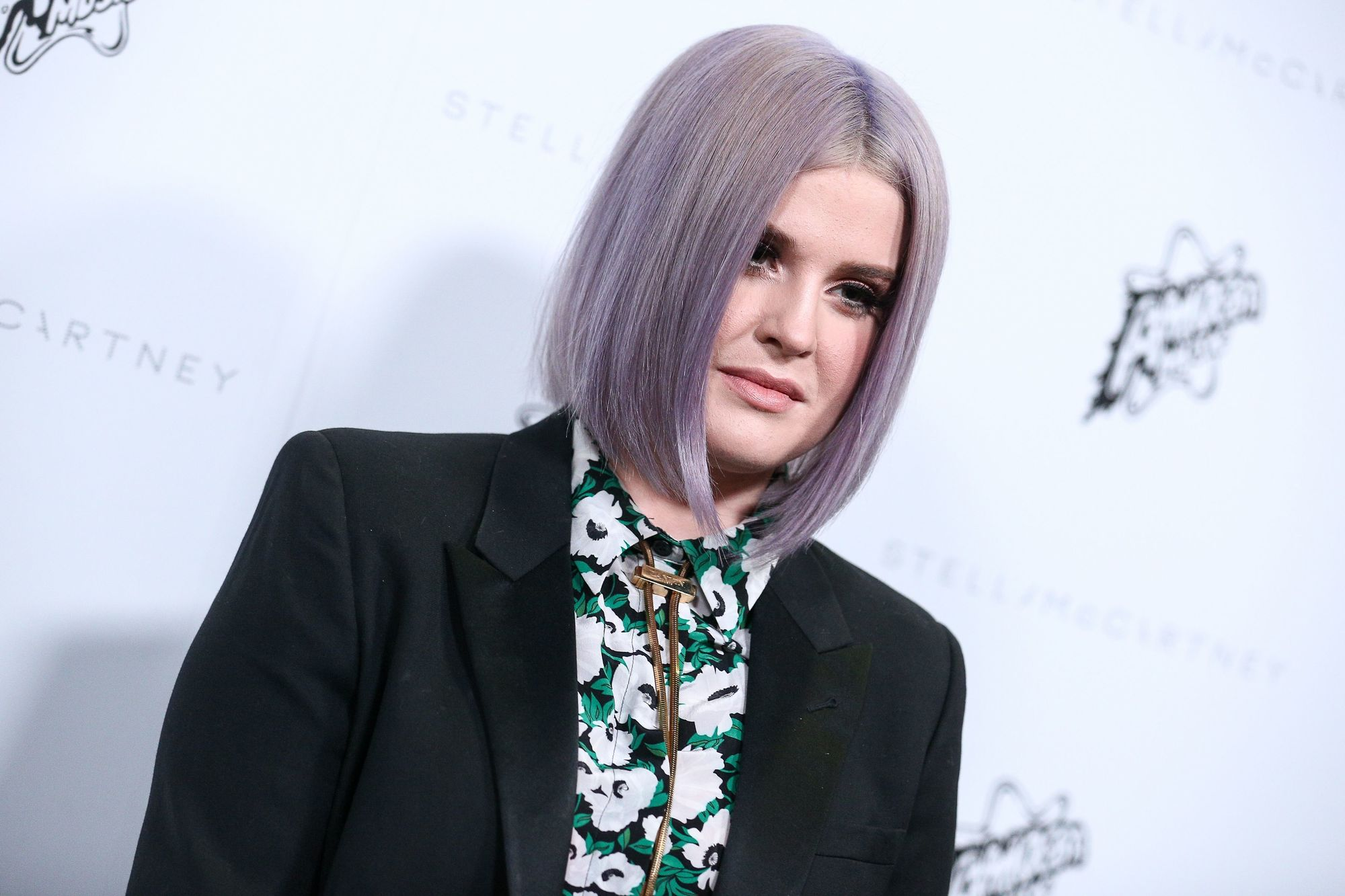 kelly osbourne in a floral shirt and black blazer with a short lilac bob