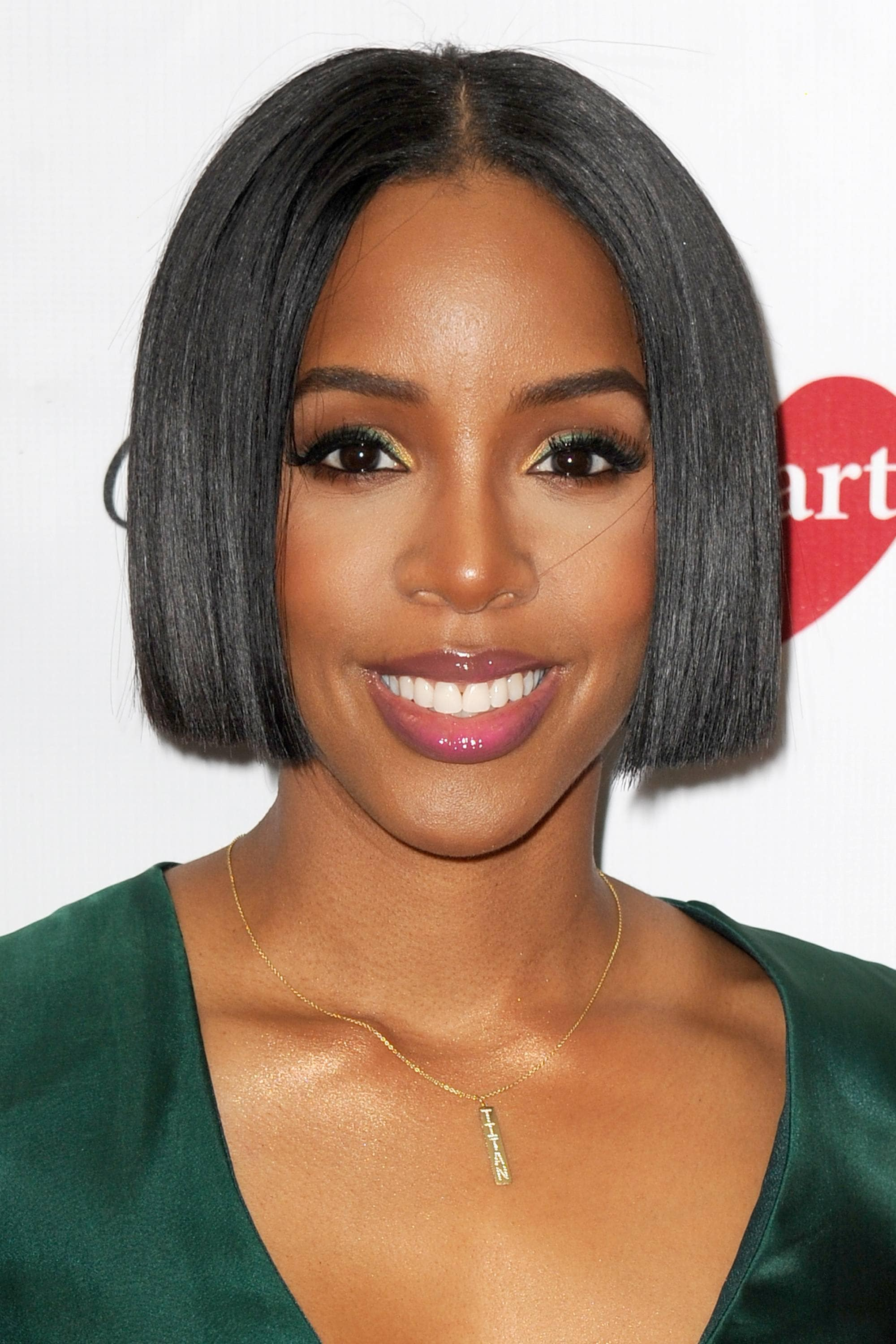 Black bob hairstyles Kelly Rowland in a green dress with her black hair cut into a short sleek chin-length bob