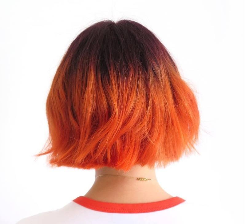 short ombre hair: model with citrus coloured orange hair and short choppy bob wearing a white t-shirt with red piping