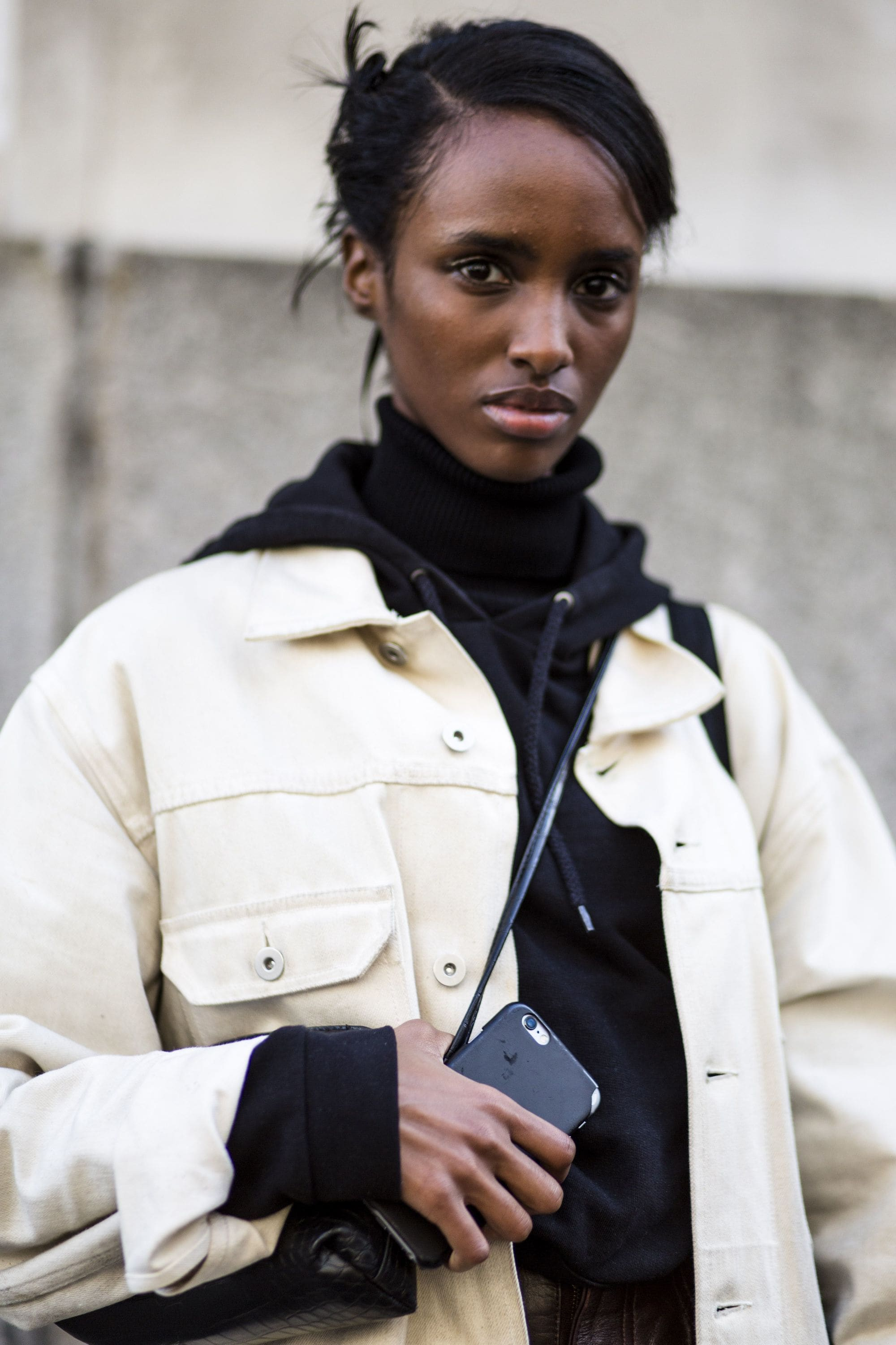 close up shot of woman with low side part hairstyle, wearing all black and white jacket at London fashion week 2018