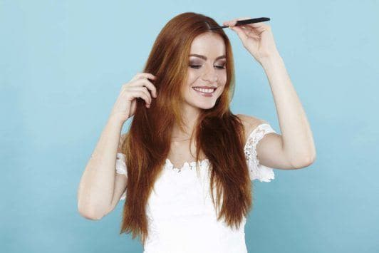 girl with long red hair creating centre parting