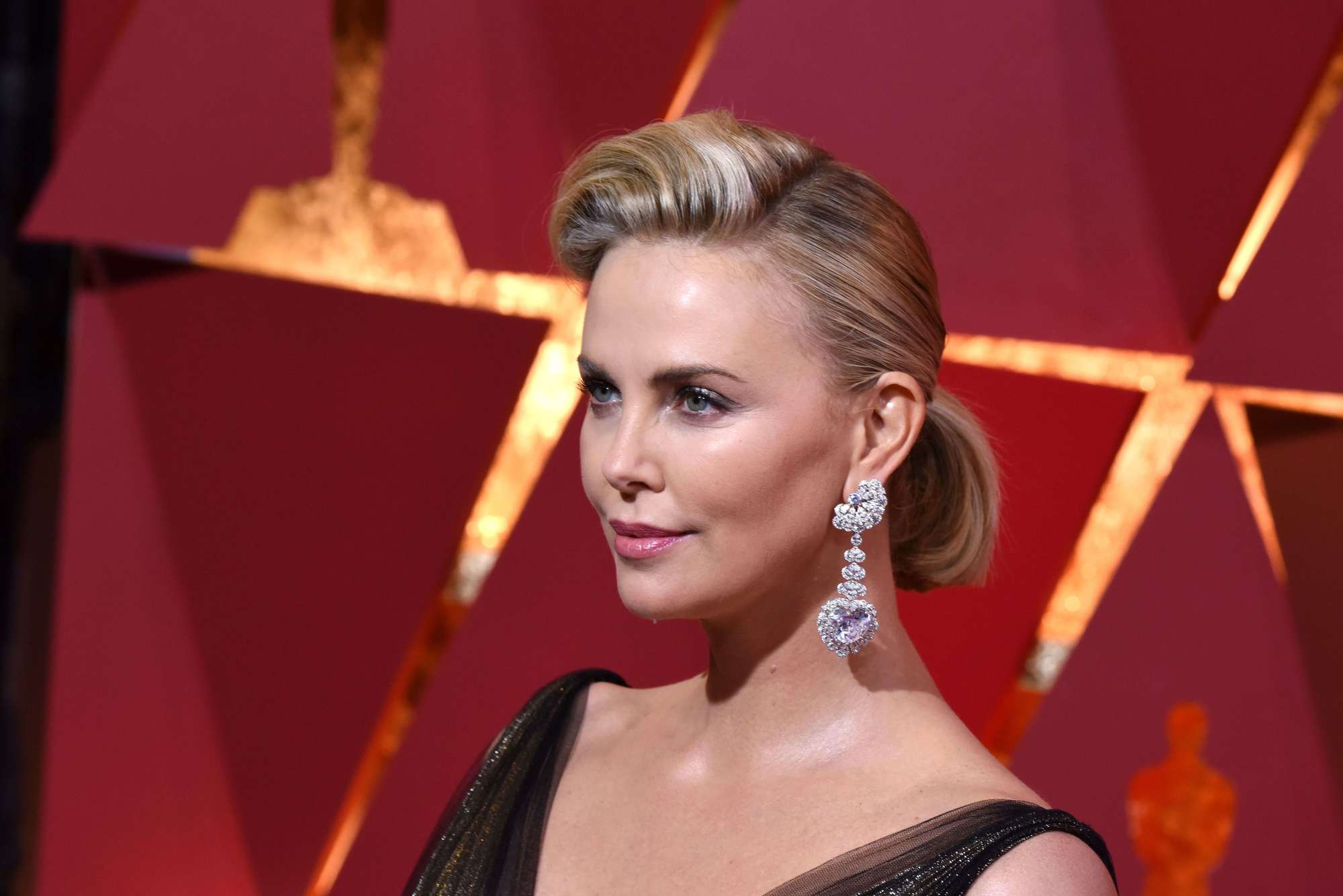 charlize theron at the oscars 2017 wearing a black dress with large earrings and her blonde hair in a quiffed ponytail
