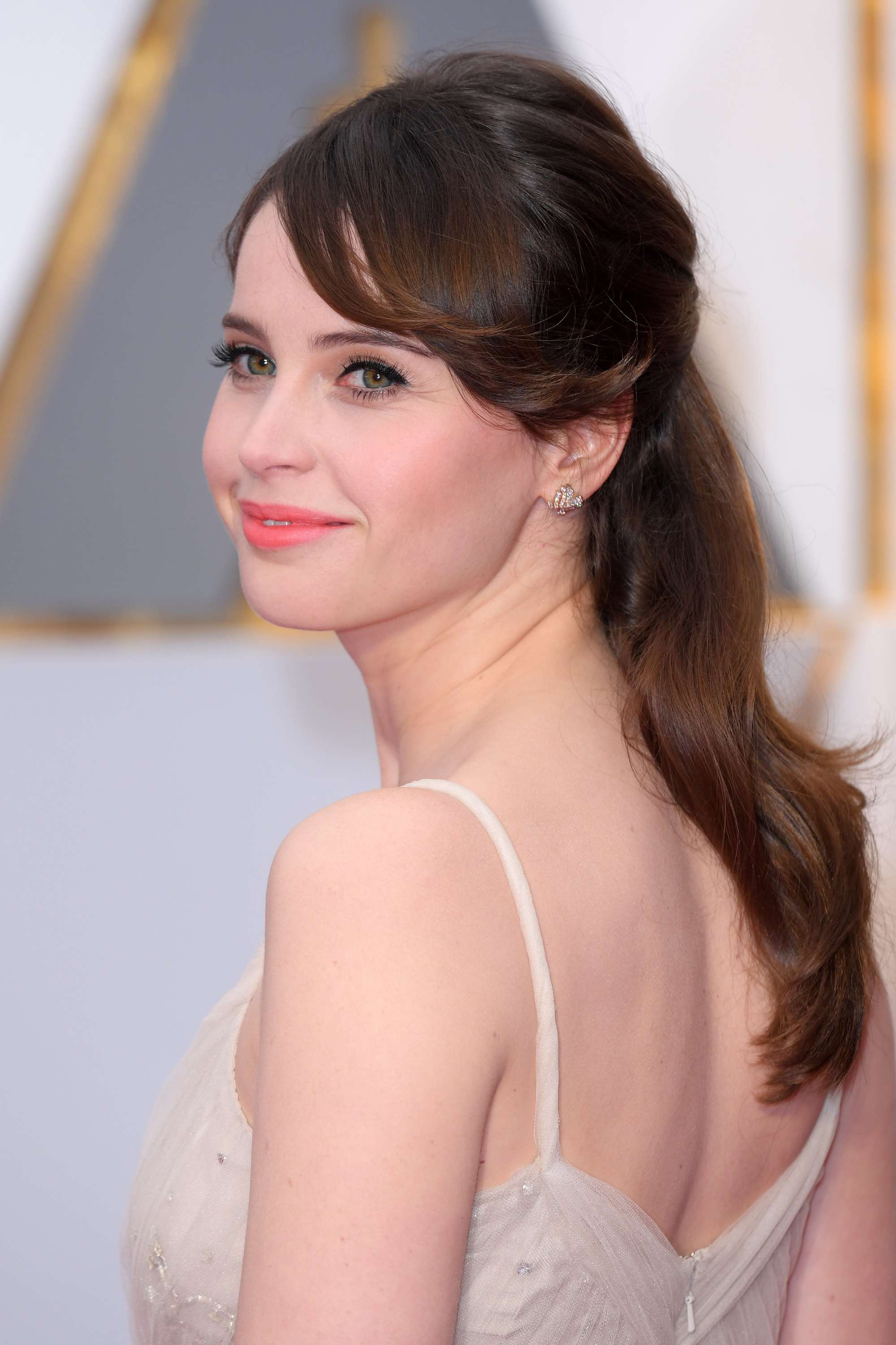 felicity jones wearing a cream glittery dress with her brunette hair in a half up half down hairstyle