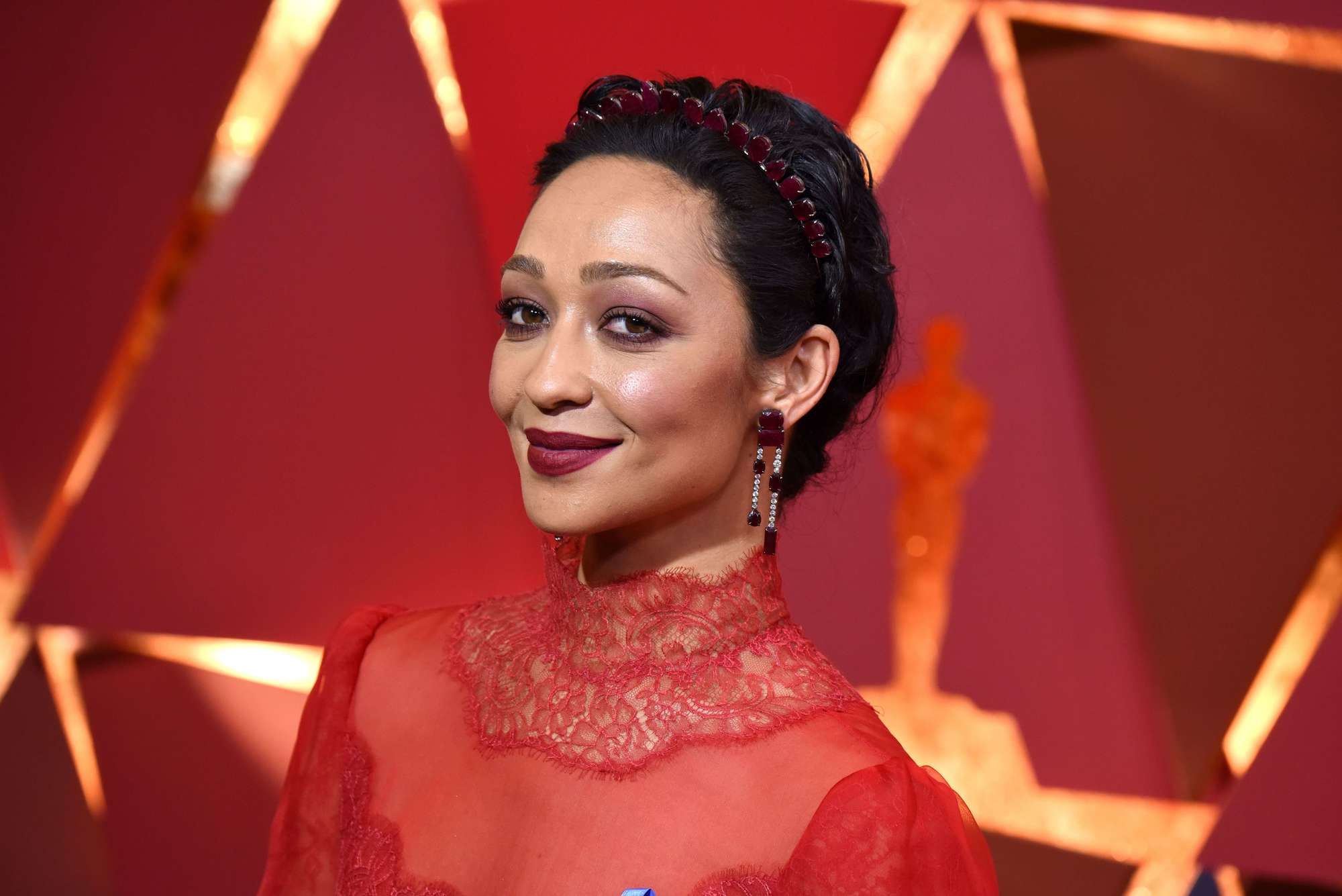 ruth negga at the oscars 2017 wearing a high neck sheer red lace dress with her hair in an updo with red hairband