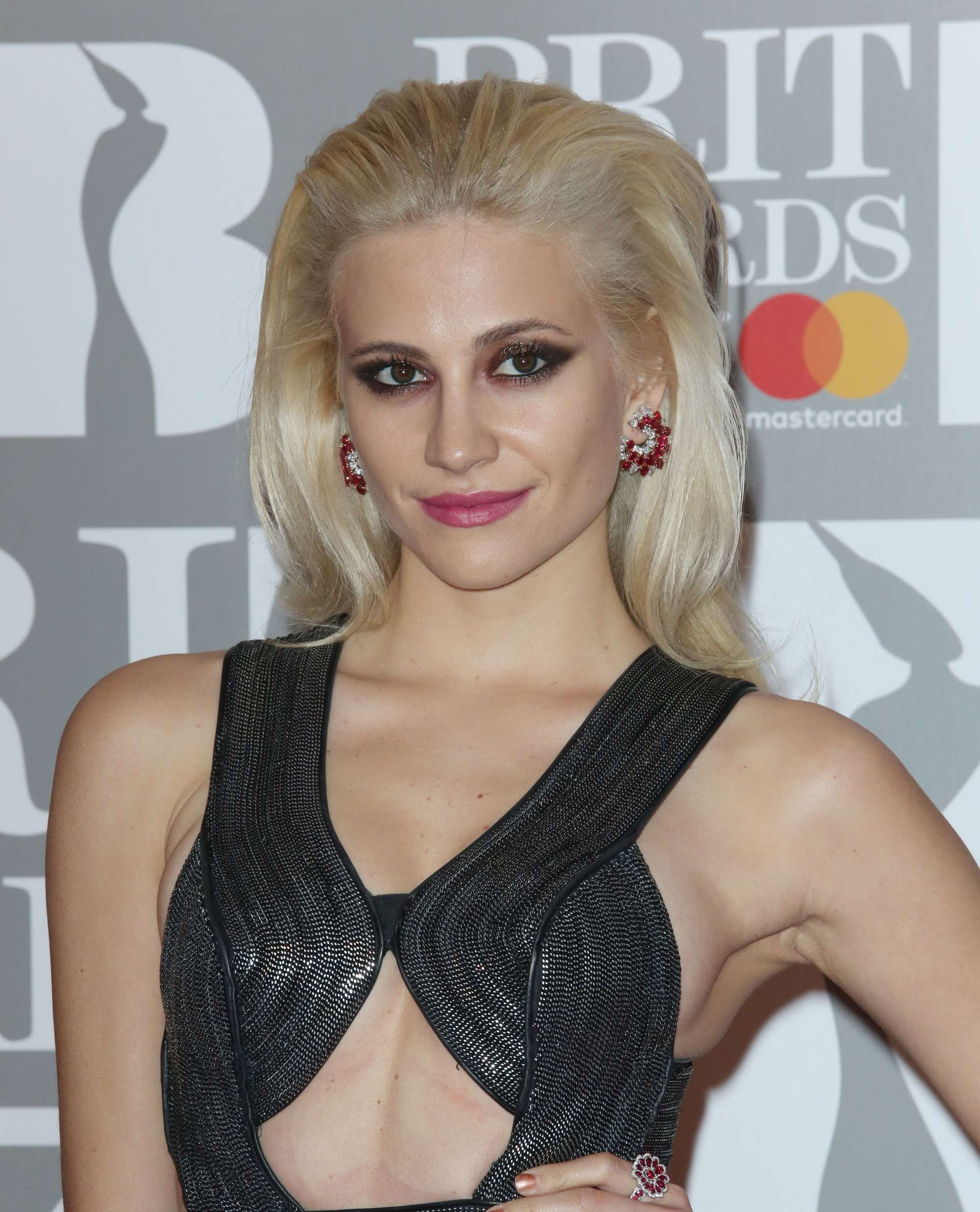 close up shot of Pixie Lott with slicked back blonde hair, wearing all black on the brit awards 2017 red carpet