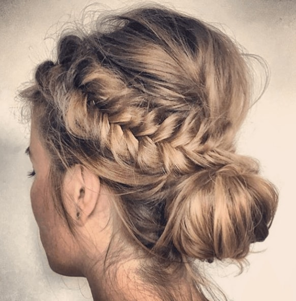 Club hairstyles: Back view of a woman's head with dirty blonde hair in braids and a loose bun