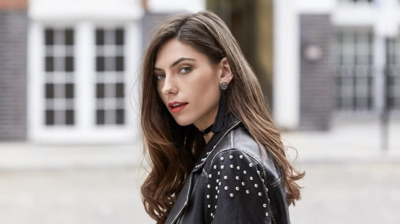 Thicker hair products: Close up shot of woman with loose curly brown hair, wearing a leather jacket and tassel earrings and posing outside
