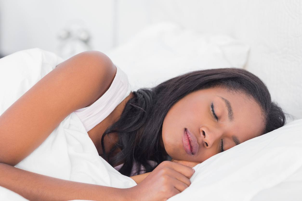 black woman with shoulder length brunette hair wearing white top sleeping