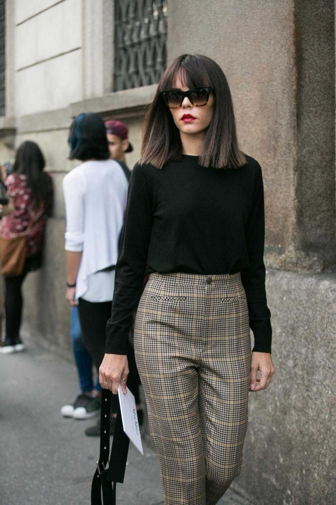 Bob haircuts for thick hair inspo woman outside walking on street with bob