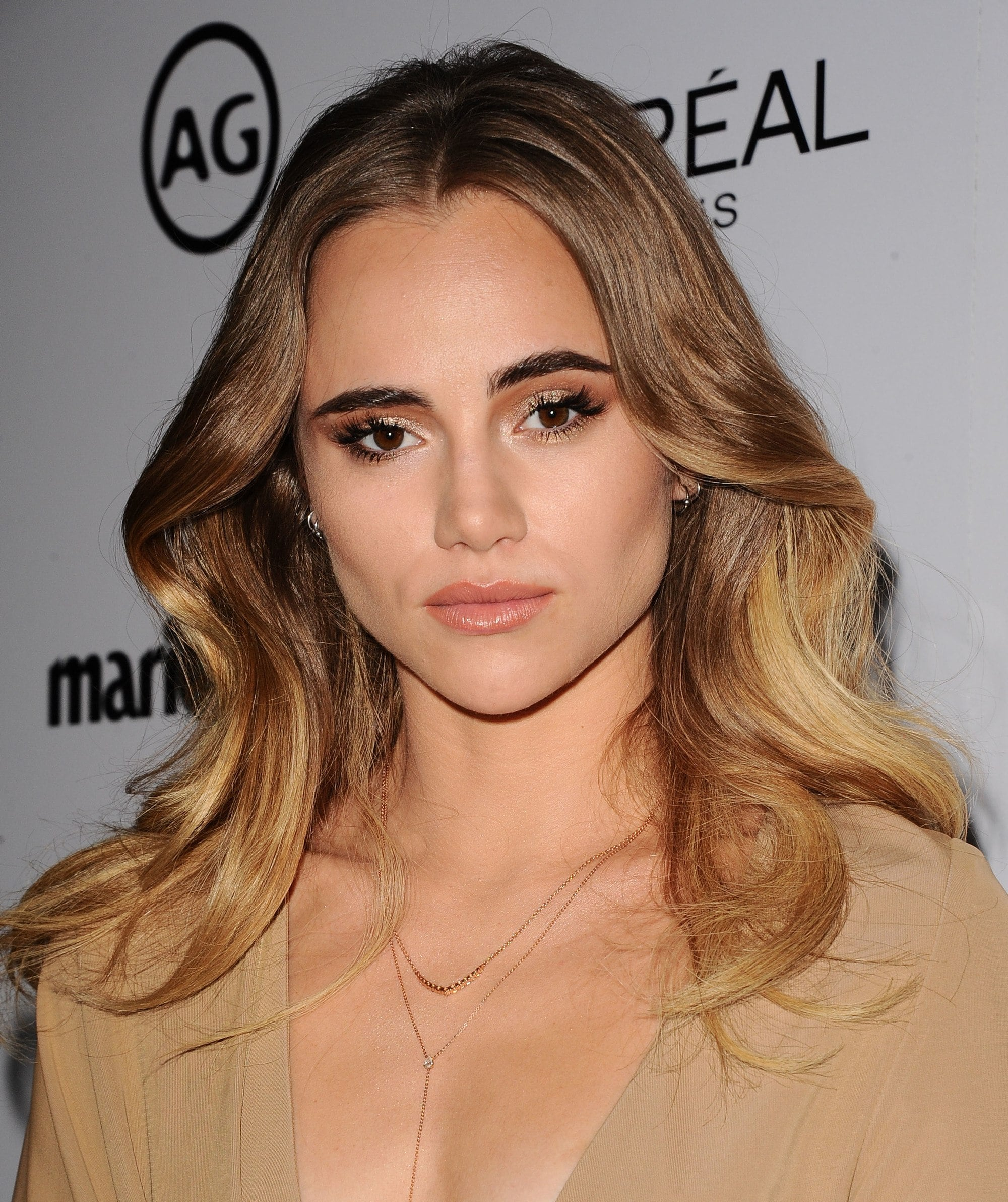 suki waterhouse wearing a camel dress with long curly bronde hair colour