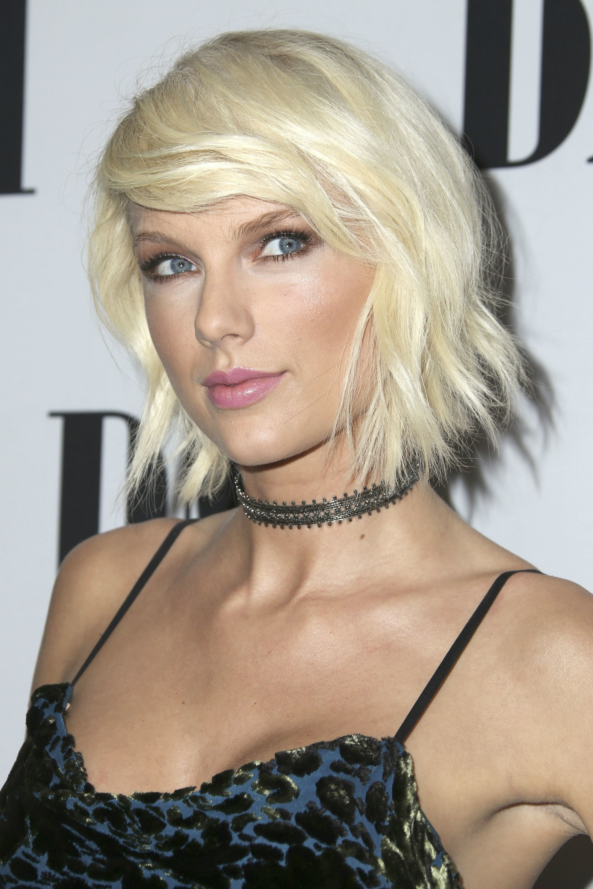 Taylor Swift in a leopard print slip dress with platinum blonde curly bob hair