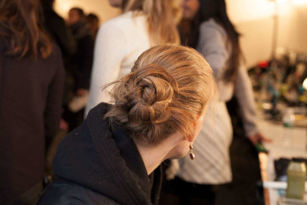 back view of a model with blonde-brown hair wearing a twisted bun hairstyle