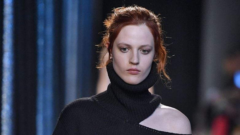 model wearing black outfit and twisted bun hairstyle on chestnut brown hair