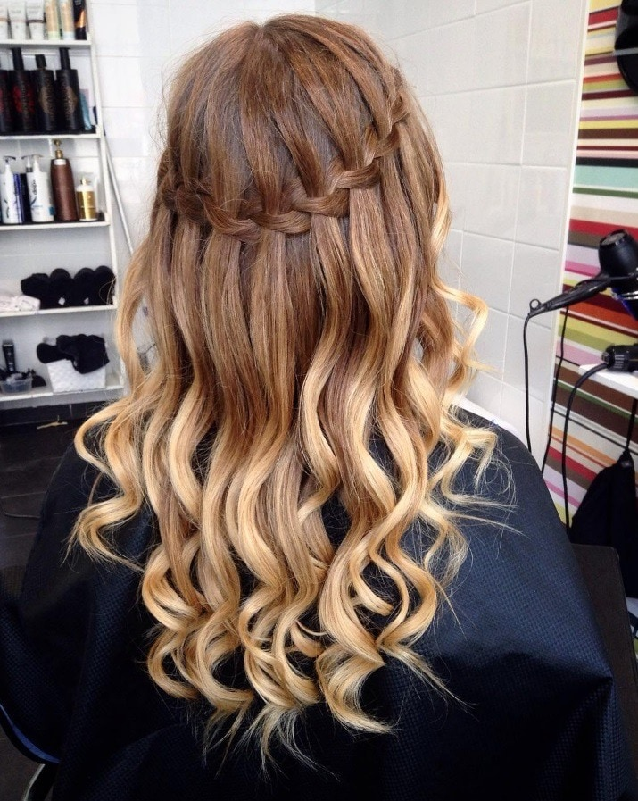 Waterfall hairstyle: woman with ombre brunette and blonde hair styled into a waterfall braid