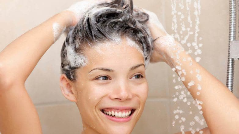 Woman lathering shampoo into her hair