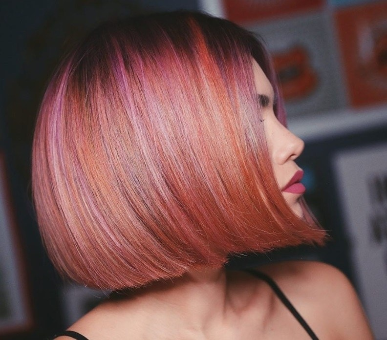 Short ombre hair: Woman with peachy multi coloured straight bob hair.