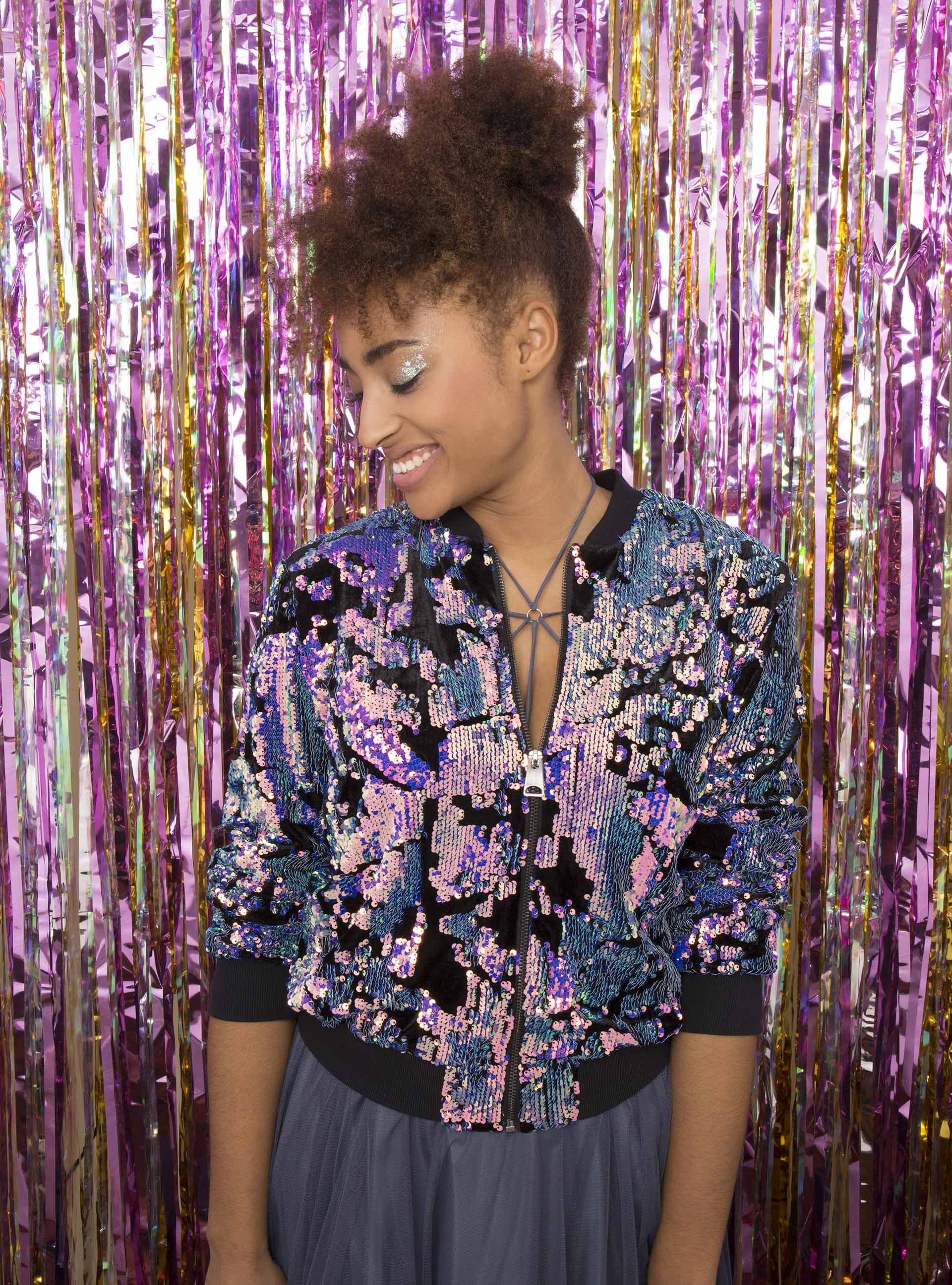 Curly prom hairstyles: Natural haired model with pinapple updo wearing a floral bomber in front of a party curtain